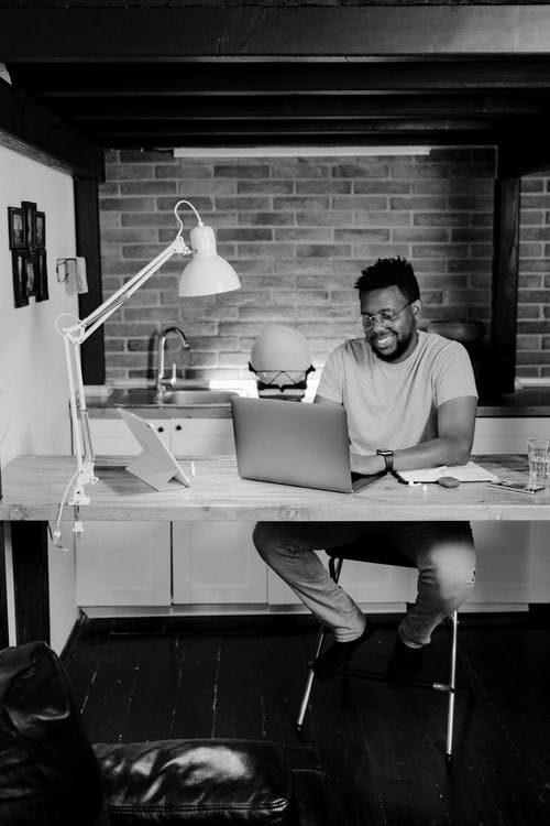 Grayscale Photo of a Man Working From Home