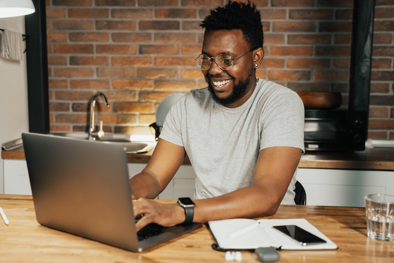 foto de um homem negro mexendo no computador para representar o conteúdo sobre softwares de gestão financeira