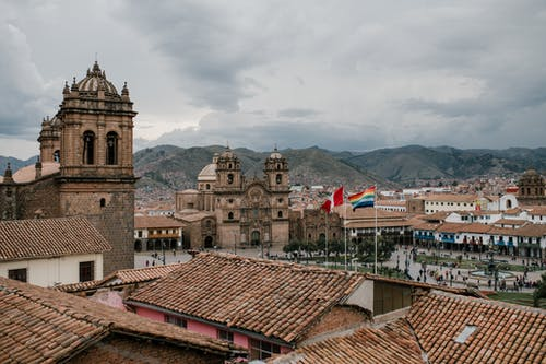 Cityscape of medieval church and houses with old tile roof in Cusco Peru