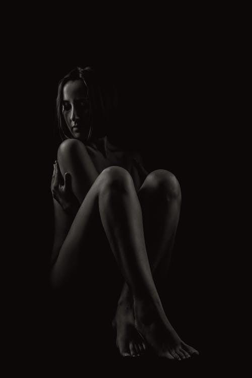 Young naked woman in dark studio