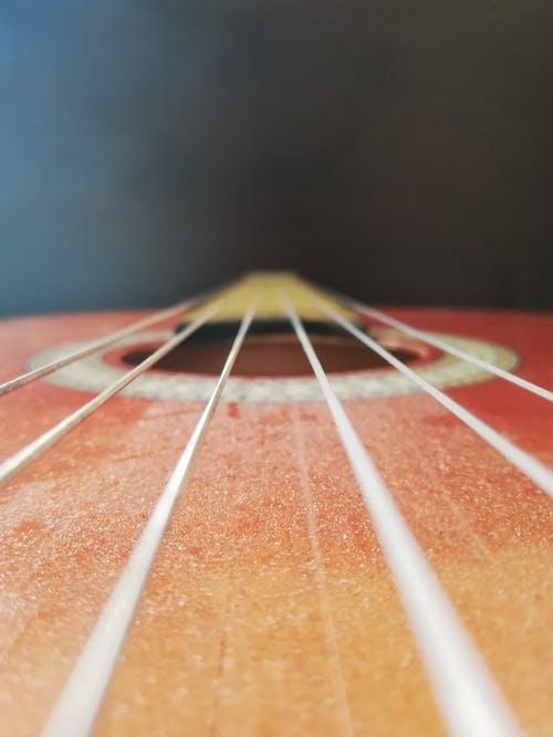 adam gitar çalıyor, ahşap gitar, bakış açısı içeren Ücretsiz stok fotoğraf
