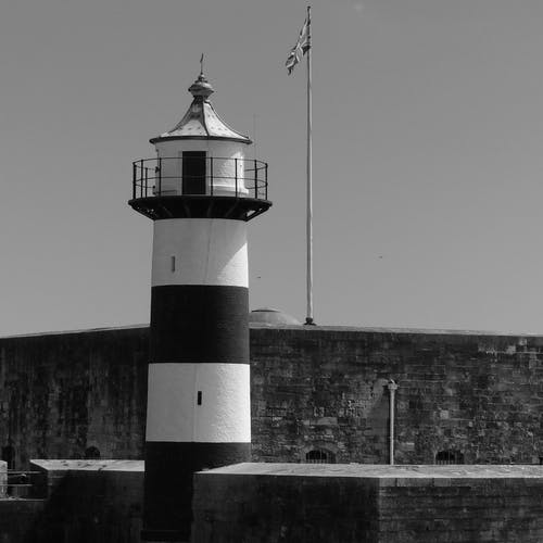 Grayscale Photo of Lighthouse Near Body of Water