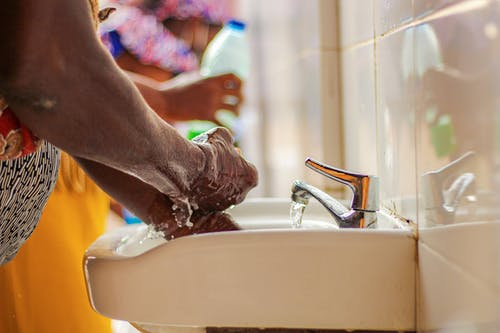 Side view of crop unrecognizable ethnic person in colorful apparel washing hands with soap in sink