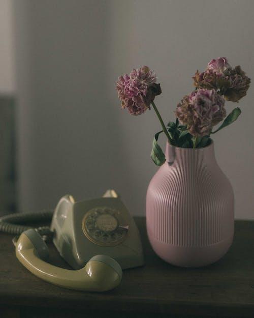 Pink Flowers in Yellow Ceramic Vase Beside White Rotary Phone