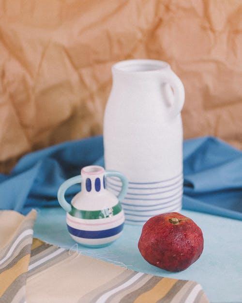 Red Apple Beside White Ceramic Mug on Blue and White Ceramic Saucer