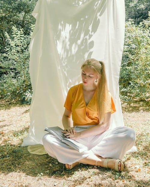 Femme En Chemise Jaune Assis Sur Le Terrain De L'herbe Verte
