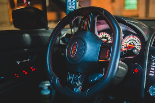 Black interior of contemporary automobile with steering wheel and illuminated dashboard with control panel in evening time with blurred street outside