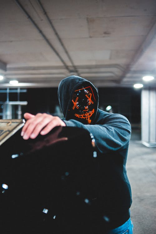 Unrecognizable male in hood wearing scary mask standing on underground parking lot near open trunk of black car on street