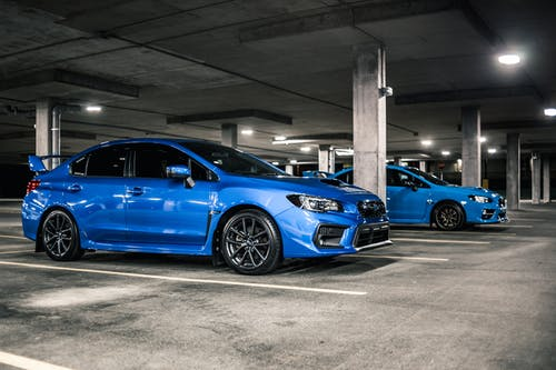 Side view of expensive blue cars with black modern disks and spoilers on trunks parked on underground parking lot with columns