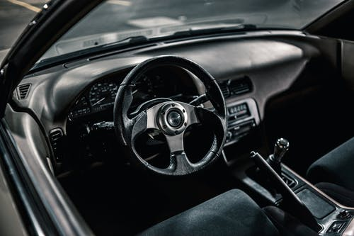 From above of black interior of aged automobile with steering wheel and manual transmission with dashboard parked on asphalt road
