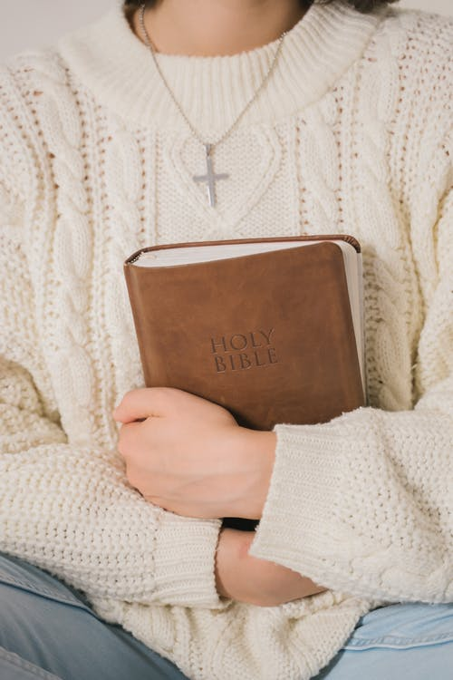Woman in White Sweater Holding Brown Leather Book