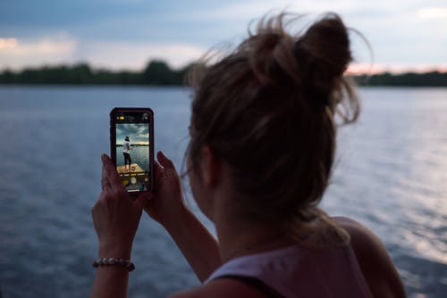 Woman Holding Iphone 6 Taking Photo of Body of Water