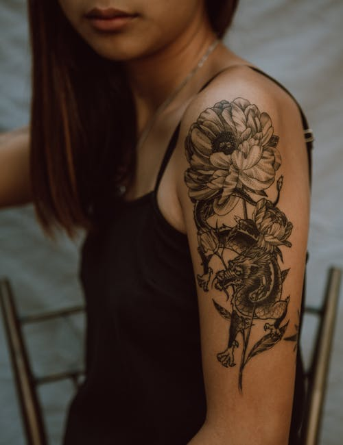 Woman showing creative tattoo on arm