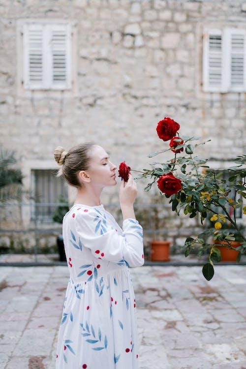 Frau, Die Blumen In Der Straße Riecht