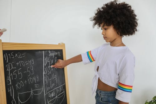 Side view of pensive black girl pointing at mathematical example on blackboard at light room in daytime