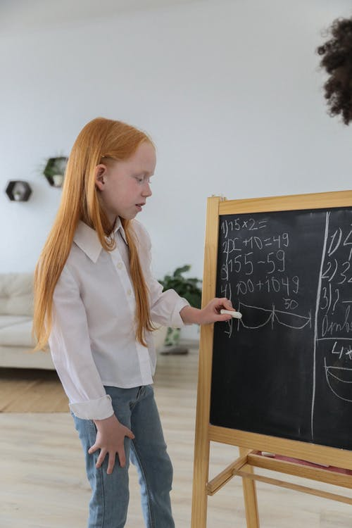 Concentrated schoolgirl standing near easel blackboard and writing mathematical equation in cozy light room