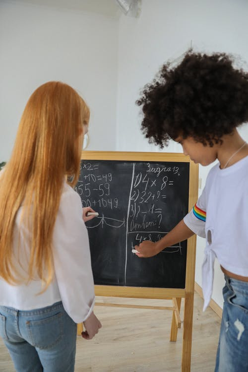 Multiethnic girls writing mathematical equations on chalkboard