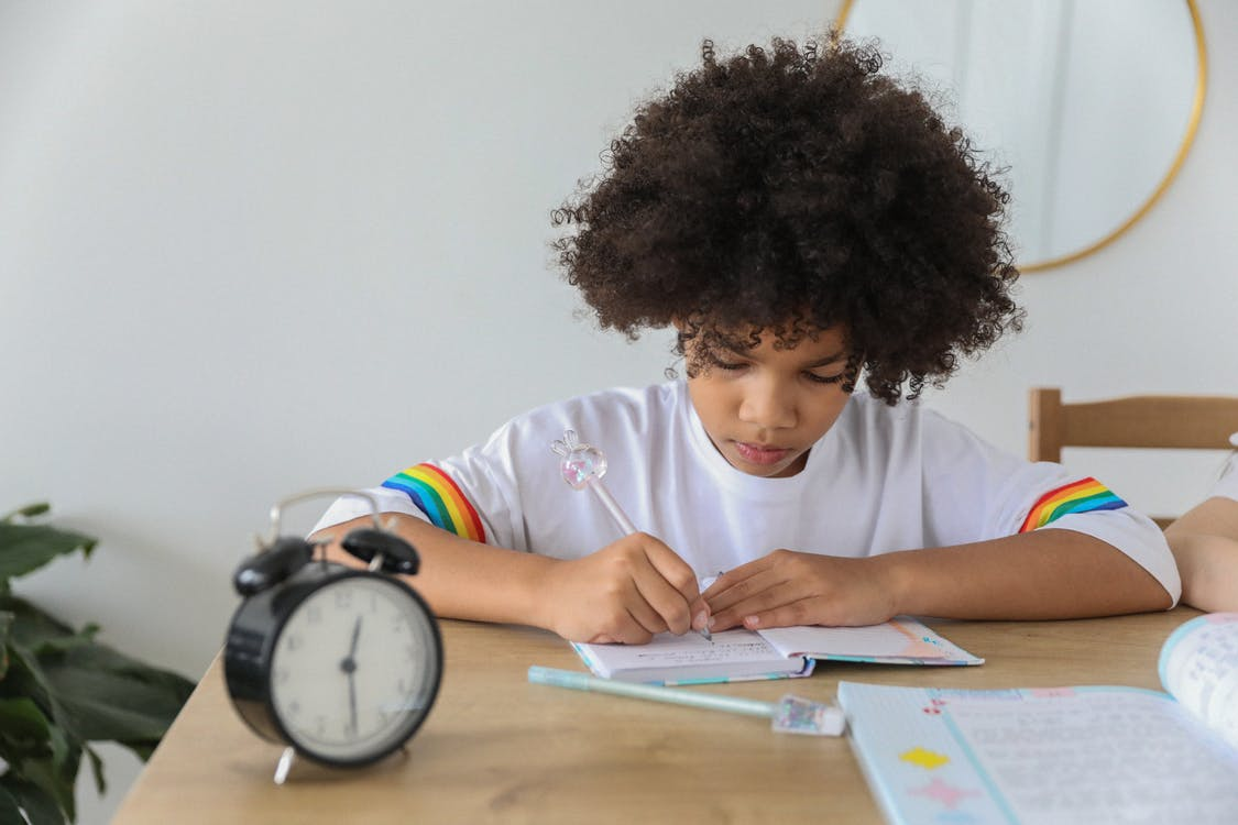 Concentrated African American child writing in notebook while studying at desk with alarm clock at home