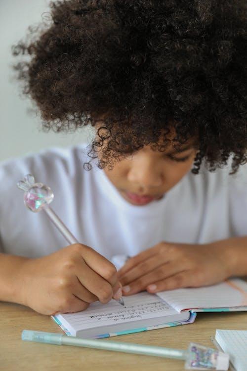 Crop African American schoolgirl writing in diary at desk