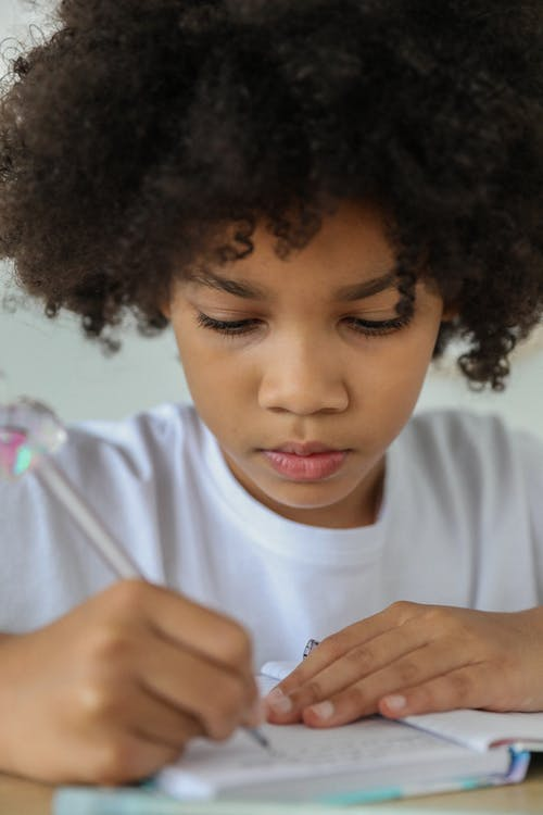 Crop attentive African American schoolgirl taking note in diary while studying at desk in daylight