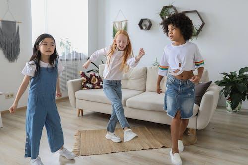 Happy multiethnic girlfriends dancing on floor at home