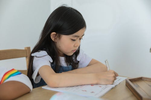 Concentrated ethnic schoolkid writing in activity book with pen while studying at table near unrecognizable black friend