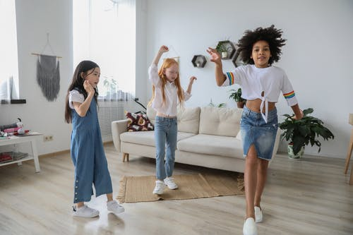 Content multiracial children dancing with raised arms on floor near sofa in living room