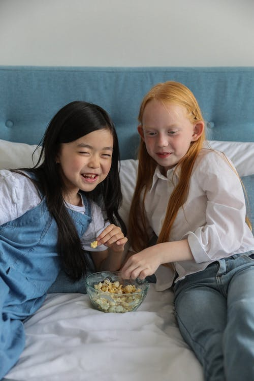 Happy Asian kid with best friend eating popcorn while spending time together on soft bed and looking away