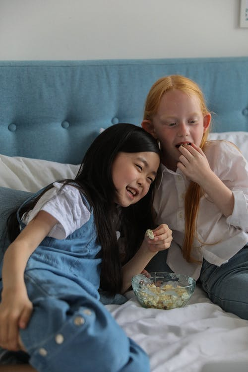 Happy diverse girlfriends eating popcorn on bed at home