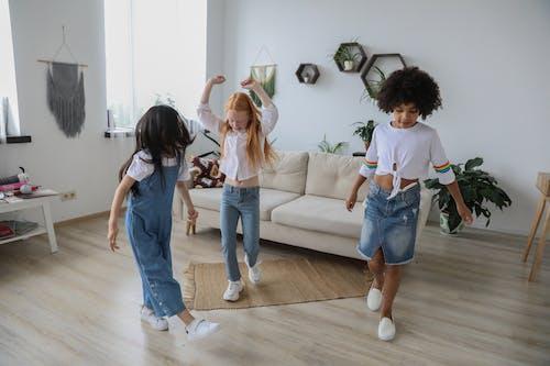 Cheerful multiethnic girlfriends near unrecognizable friend in casual denim apparel having fun in living room