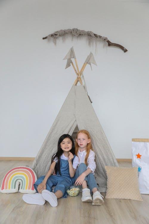 Cute little diverse children relaxing on floor near tent at home