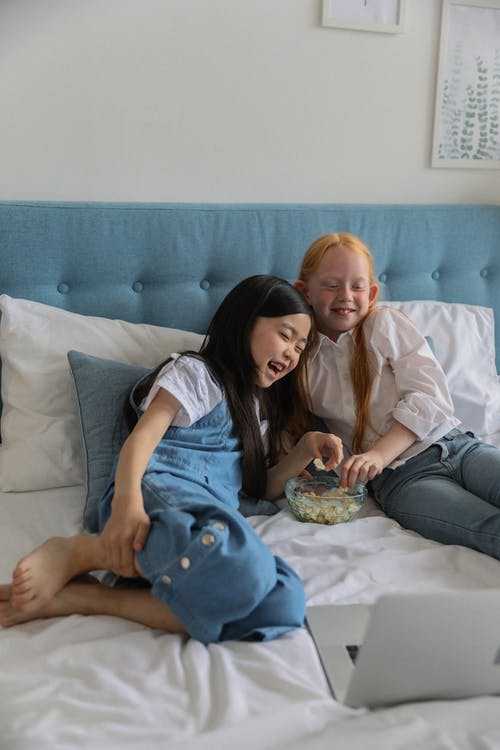 Cute multiracial children eating popcorn while lying on bed and watching funny movie on laptop