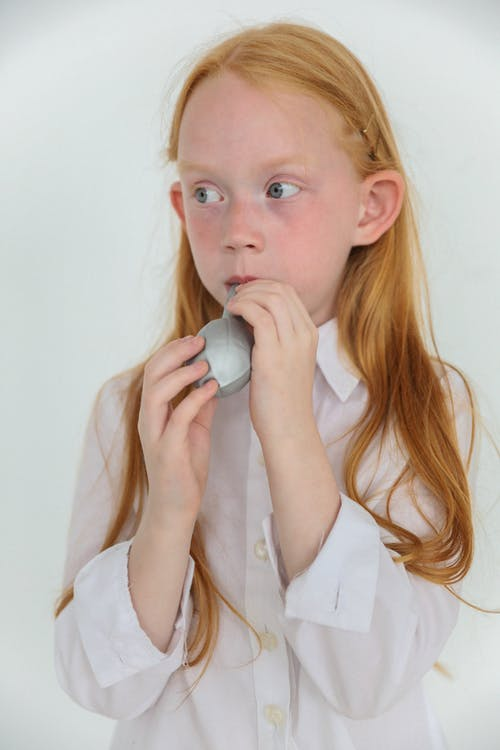 Concentrated little redhead child blowing balloon in white studio