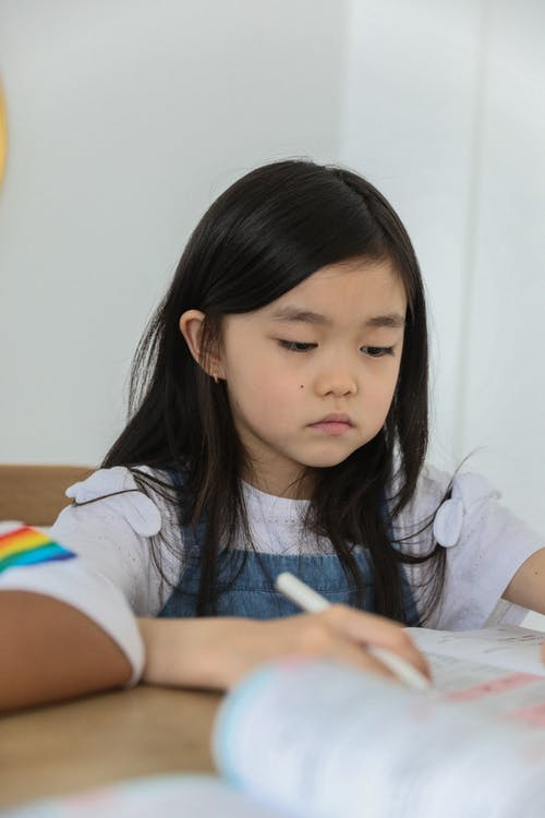 Attentive cute little Asian girl with long dark hair sitting at table and writing in copybook during lesson at school