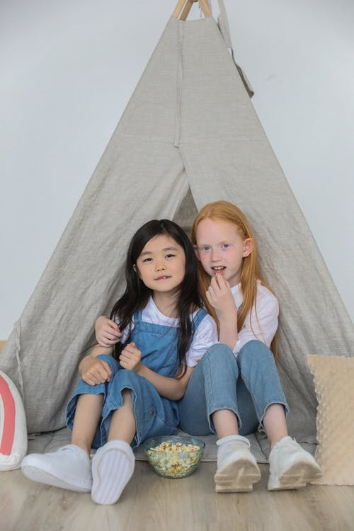 Happy little diverse children hugging and eating popcorn while playing together in tent at home