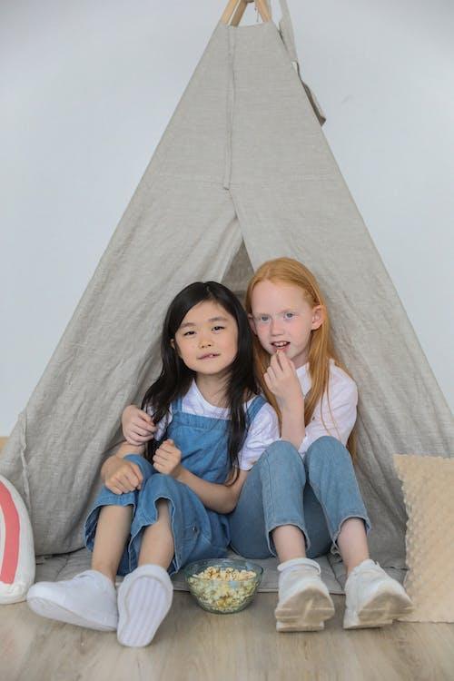 Gelukkige Diverse Kinderen Knuffelen En Eten Popcorn Tijdens Het Spelen Samen In Tent Thuis