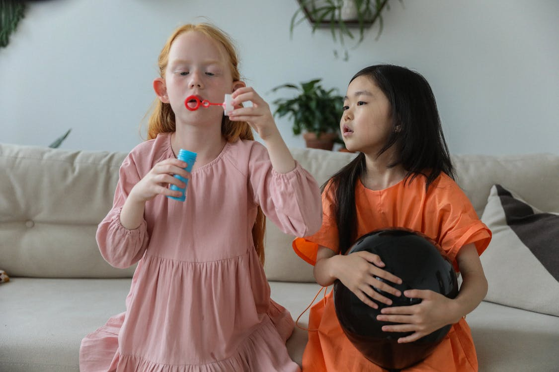 Adorable little redhead girl in stylish dress blowing soap bubbles while playing with cute Asian girlfriend holding black balloon sitting on sofa at home
