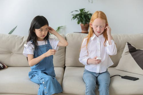 Curious multiracial children listening to music in TWS earphones while sitting on couch at home