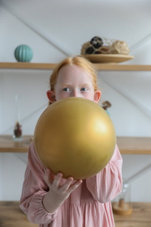 Adorable child in girlish dress inflating balloon at home