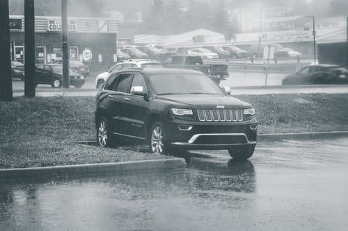 Black and white of big black modern off road sUV automobile parked on wet asphalt in city under rain in daytime