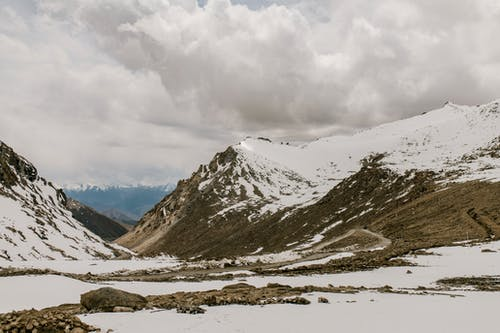 Scenery of valley covered with snow located in mountainous area against cloudy sky in countryside in nature in winter time
