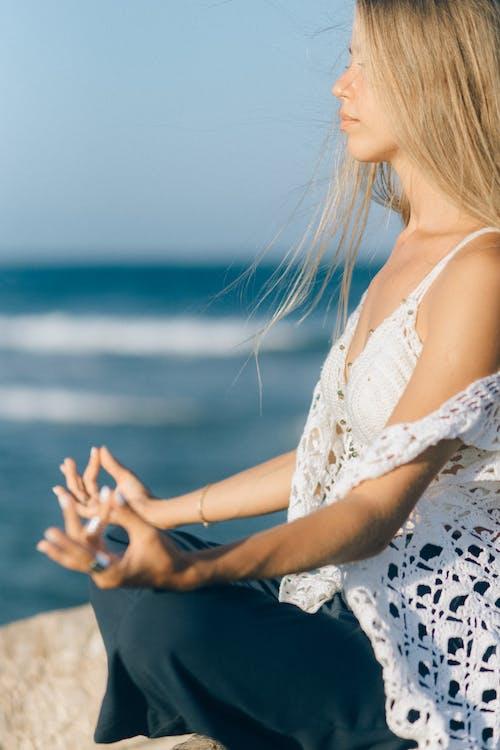 A Woman Meditating Near Sea