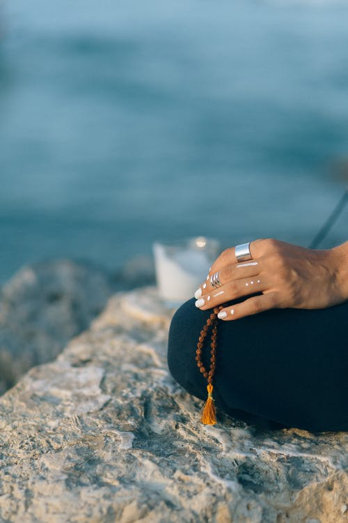 Person Wearing Silver Ring and Black Pants Sitting on Rock Near Body of Water
