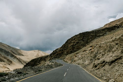 Narrow asphalt highway with marking lines running near slope among rocky formations against cloudy sky in overcast weather in nature