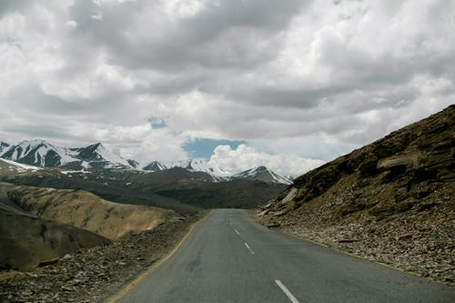 Road between snowy mountains under cloudy sky