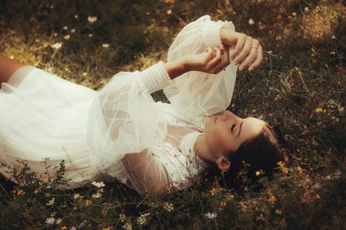 Stylish woman in white dress resting on meadow