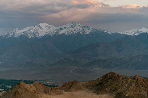 Picturesque view of high ridges with snowy peaks under cloudy sky at sundown