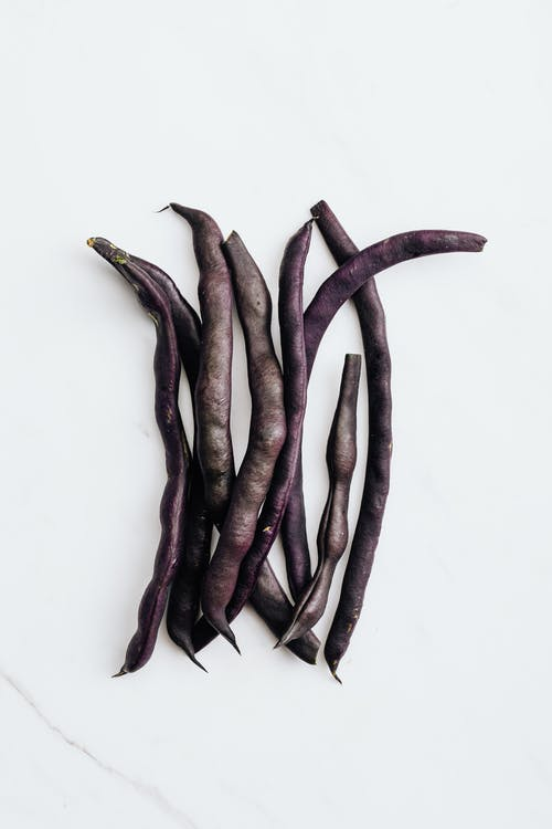 Purple Peas on White Surface