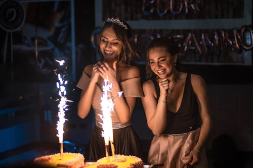 Cheerful girlfriends near birthday cakes with burning sparklers