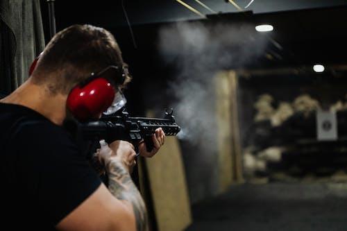Man in Black T-shirt Holding Black Assault Rifle